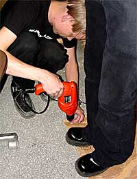 Antti presses the terrain evenly against reinforcement and Janne uses a power drill to screw the two together